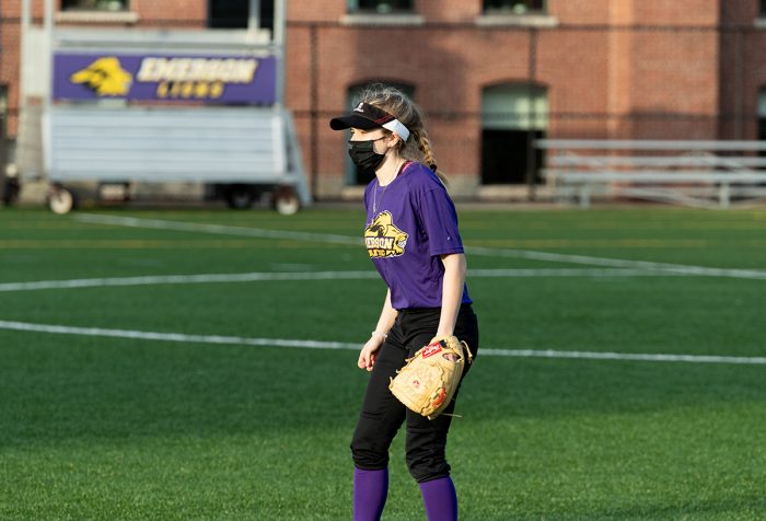 A women with a softball gloves, wearing a face mask on a softball field
