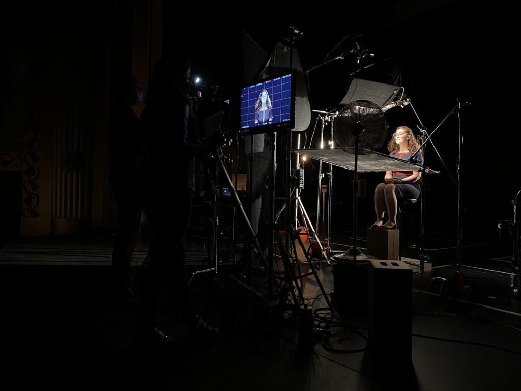 Student sits in sound stage surrounded by film equipment