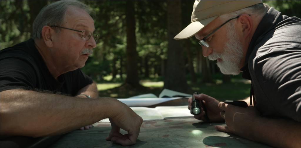 Two men look at a map together