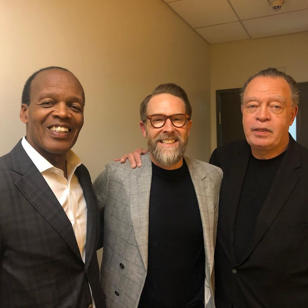 Three men stand together