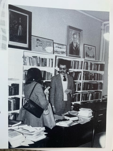 Man talks to a woman in front of a book shelf