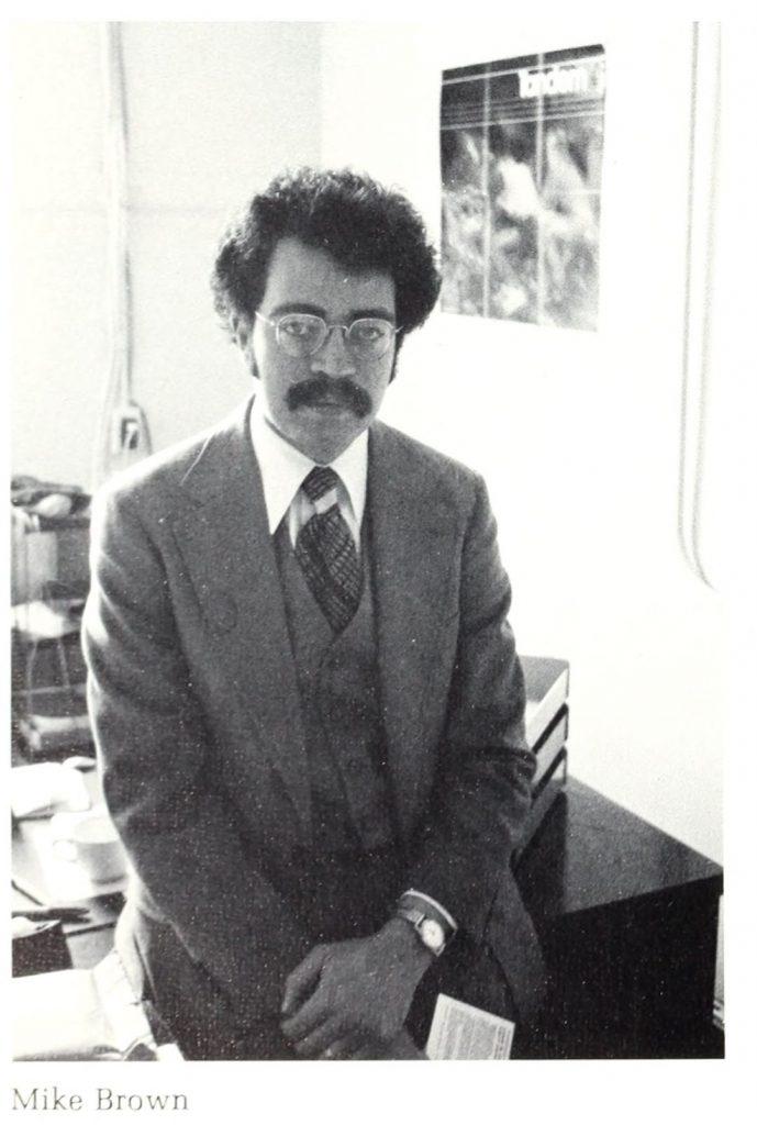 A man sits on a desk