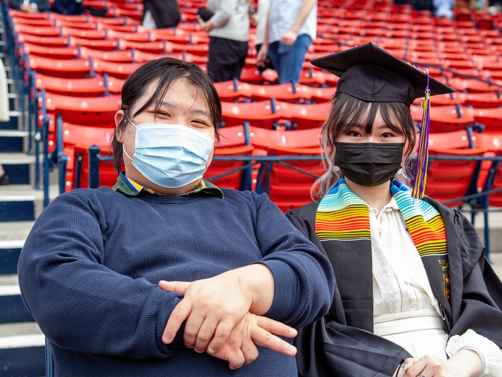 graduate in cap, gown, and mask sits in stands at Fenway next to man