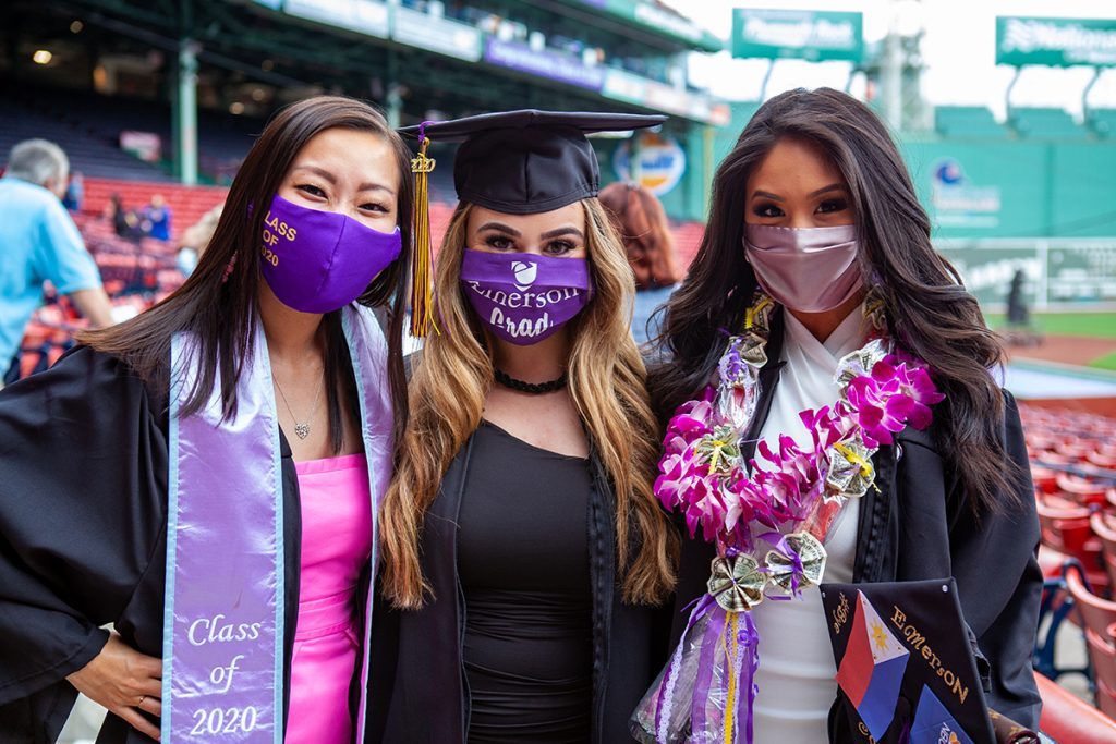 three women in gowns and masks wearing sashes and a lei