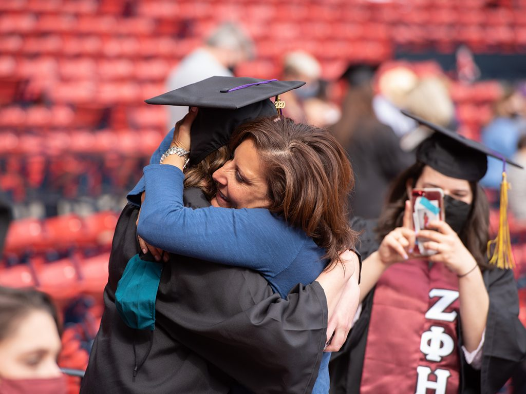 graduate and woman hug as other graduate takes photo