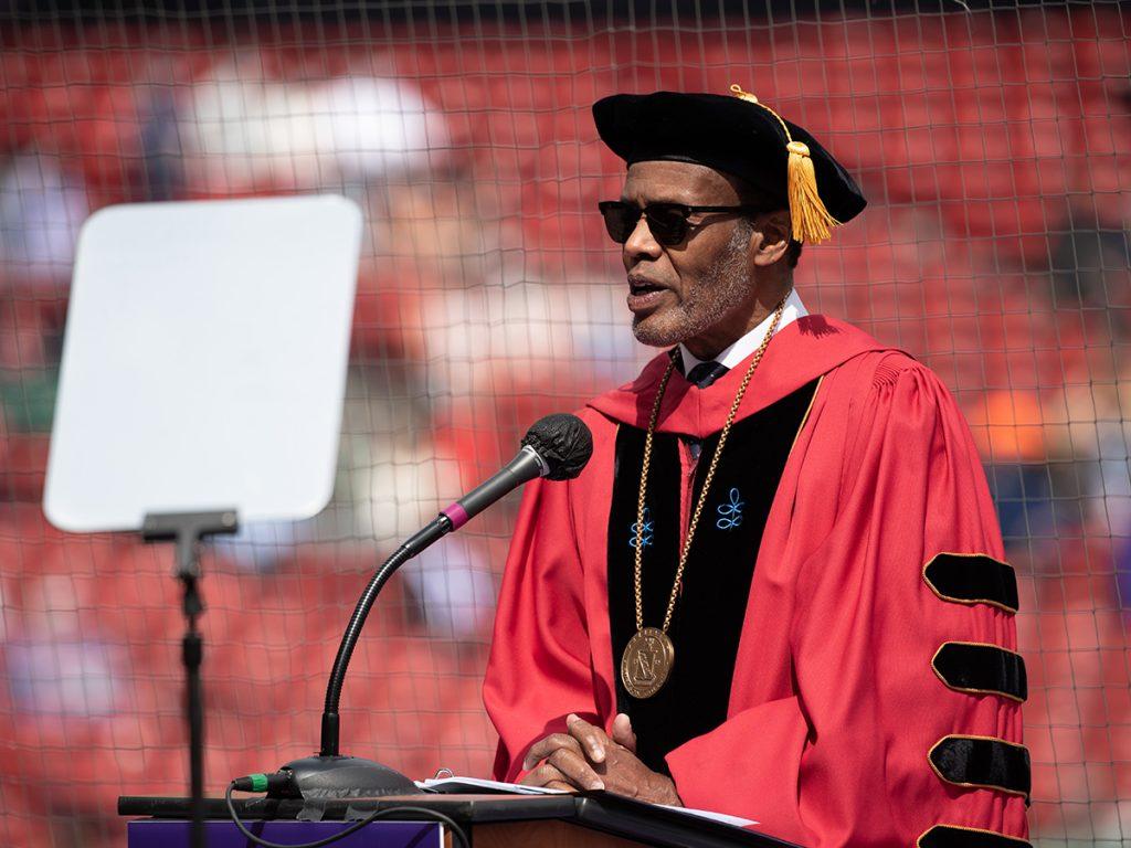 Lee Pelton in regalia and sunglasses speaks at podium at Fenway