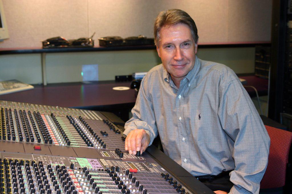 Man sits at radio mixing board