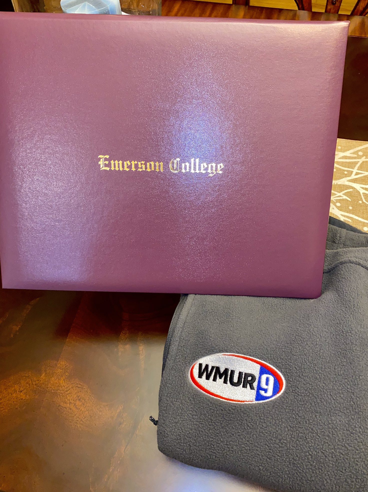 An Emerson College diploma belonging to Natalie Benoit '20 resting next to a WMUR News 9 sweatshirt, marking Benoit's next big life transition.