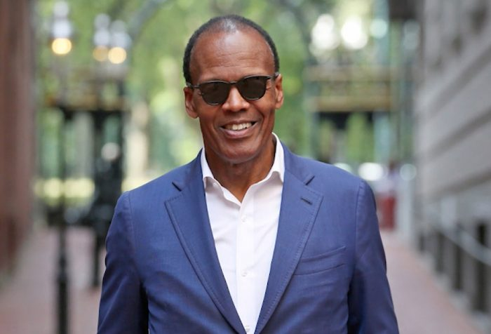 Lee Pelton in suit and sunglasses standing in Boylston Place alley