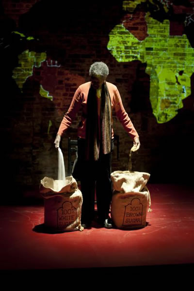Black woman on stage with head bowed, pulling sugar from two burlap sacks