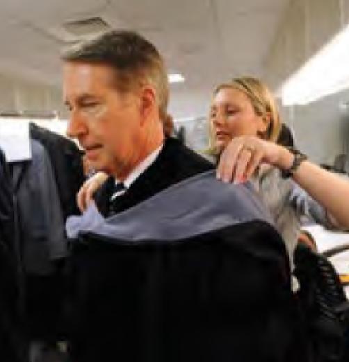 Woman helps man put on graduation garb