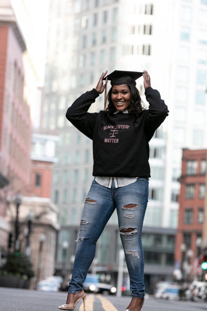 Erica Jones in Black Lawyers Matter sweatshirt and mortarboard on Boston street