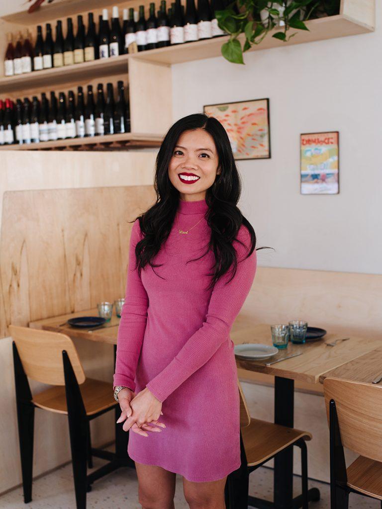 Lien Ta standing in restaurant wearing pink dress