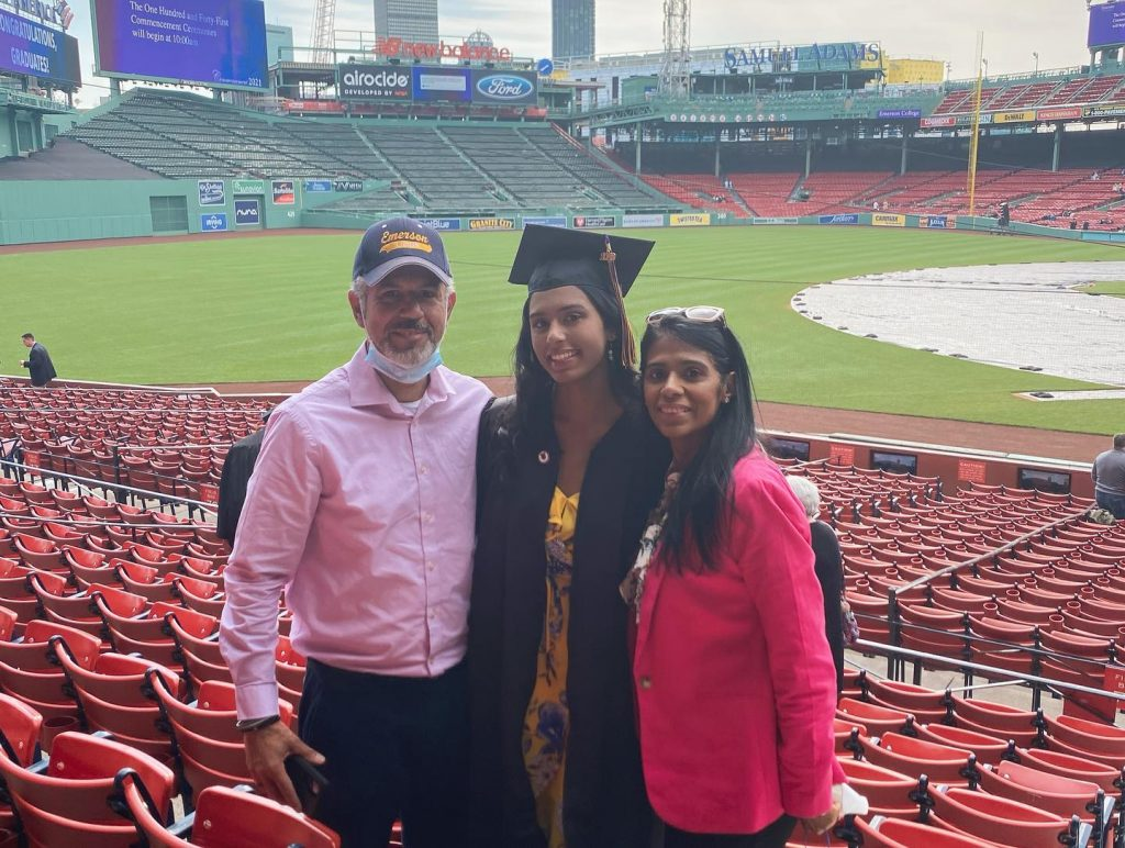 Natalie Benoit '20 stands between her father and mother during her May 2021 Emerson College Commencement inside Fenway Park,