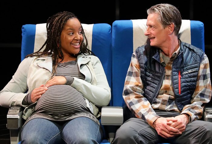 Two people act on a stage sitting in airplane seats. The woman is pregnant and the man is not. They are smiling at each other.