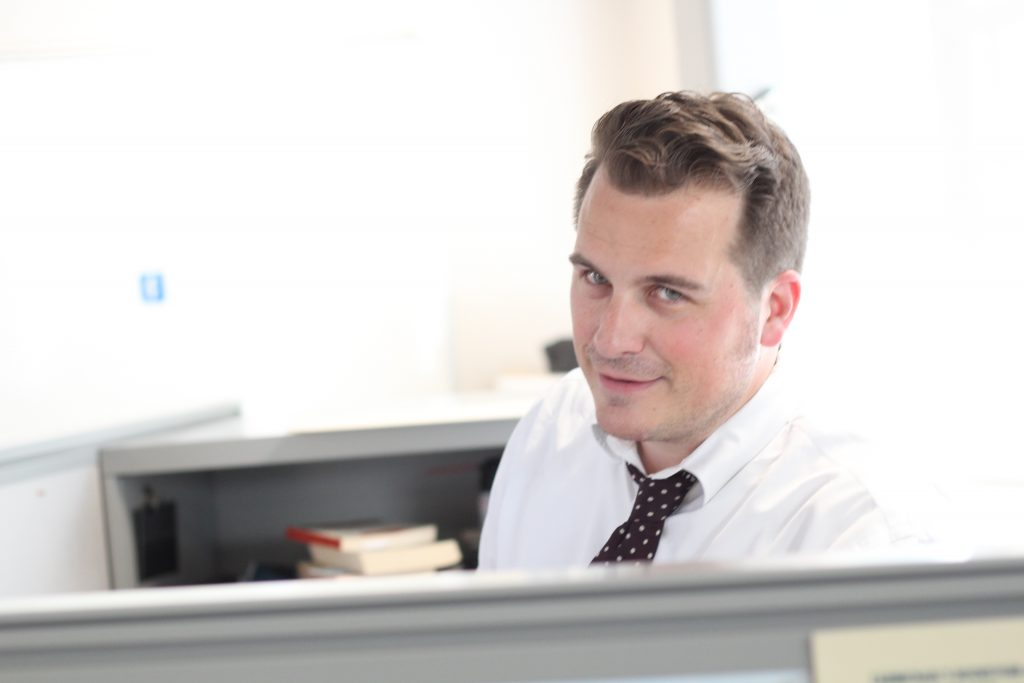 man in white shirt sitting in cubicle