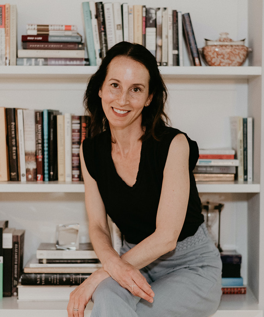 Nicole Graev Lipson sits in front of a white bookshelf