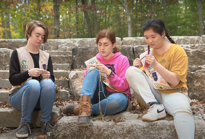 Three people sit on a stone bench together making friendship bracelets