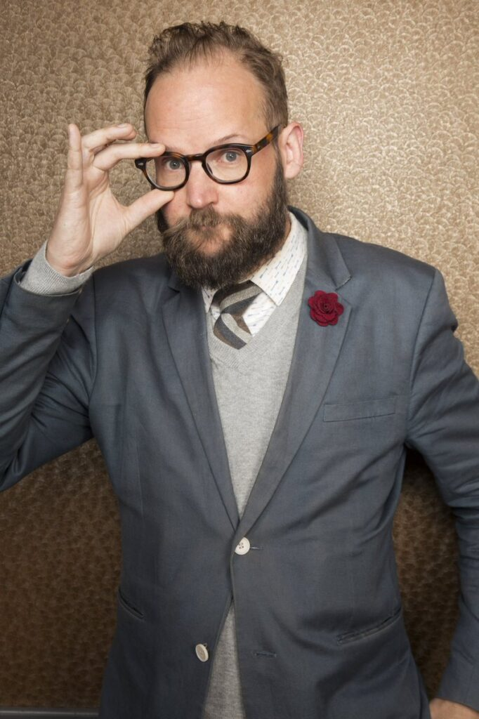 Waist up photo of man wearing blazer, touching glasses on his face