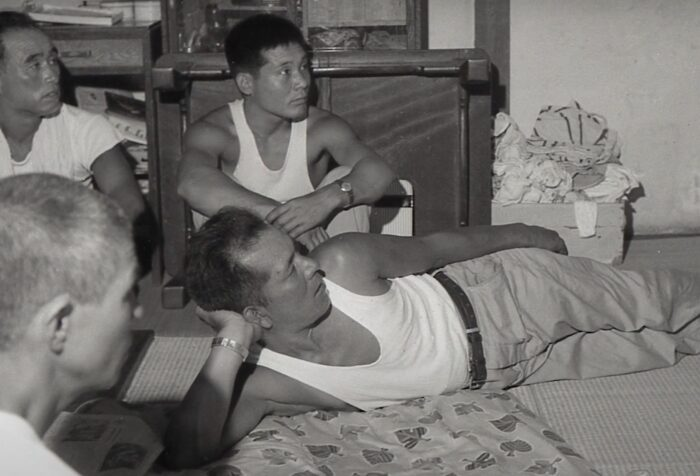 black and white image of Japanese men sitting around watching TV