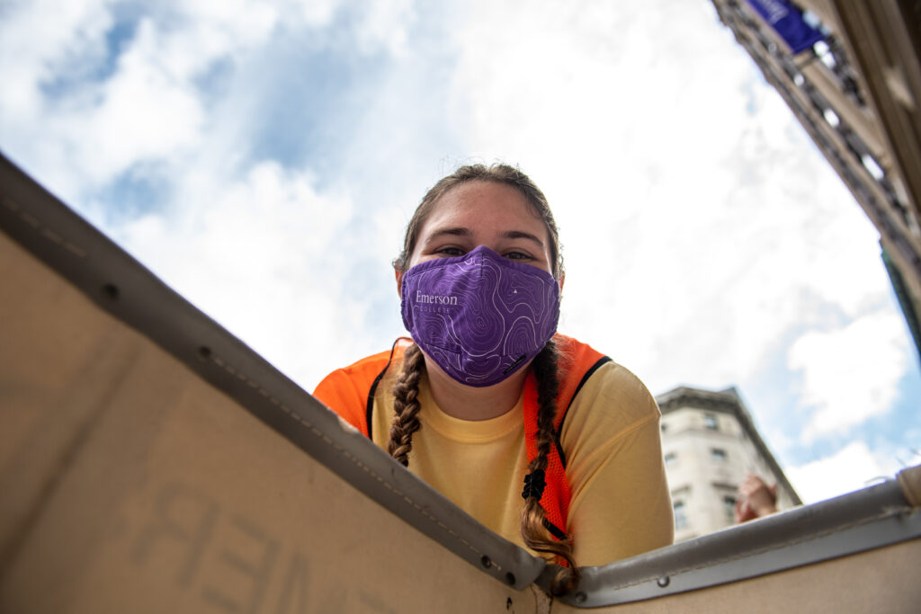 A person wears a purple mask and looks down into a cart