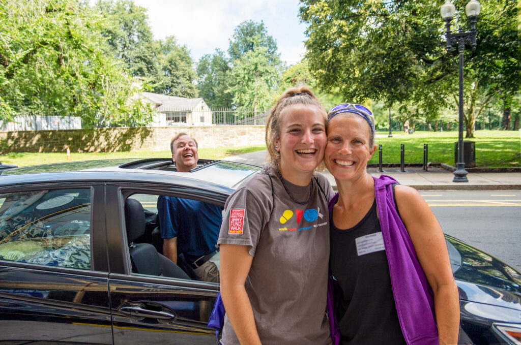 In the foreground a mother and daughter smile next to each other while the dad pokes his head out of a car sunroof in the background
