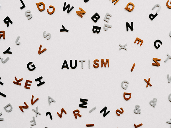 graphic of scattered letters, with six in the middle spelling autism