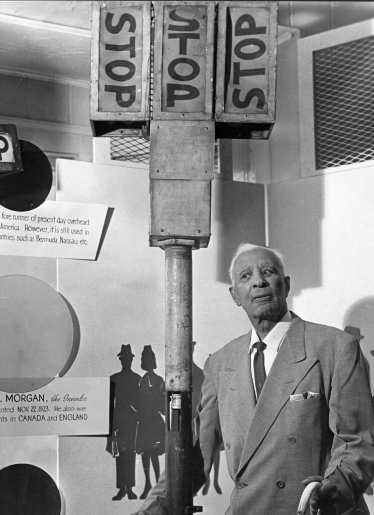Cleveland, Ohio native and inventor Garrett Morgan poses with his award-winning  patent, a three-position traffic signal.