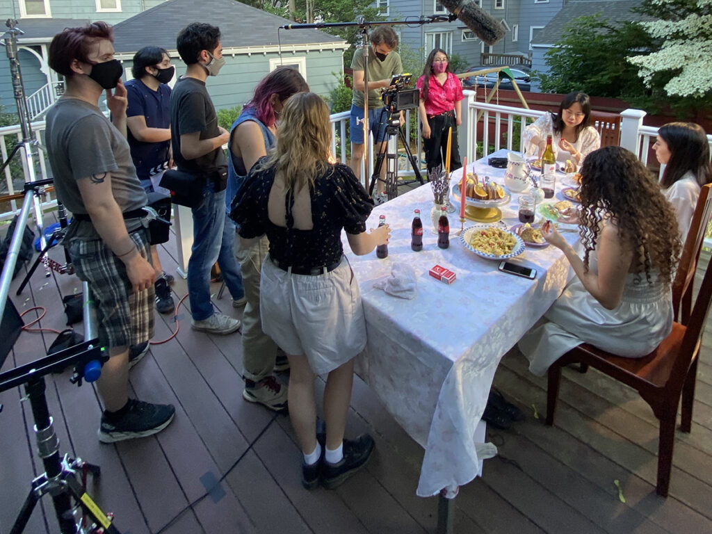 cast and crew around a table covered with food on a deck