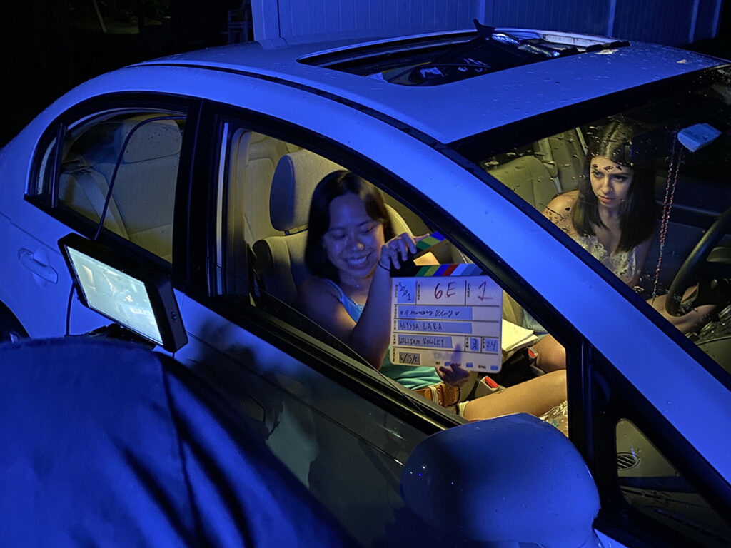 Two women sit in car at night.