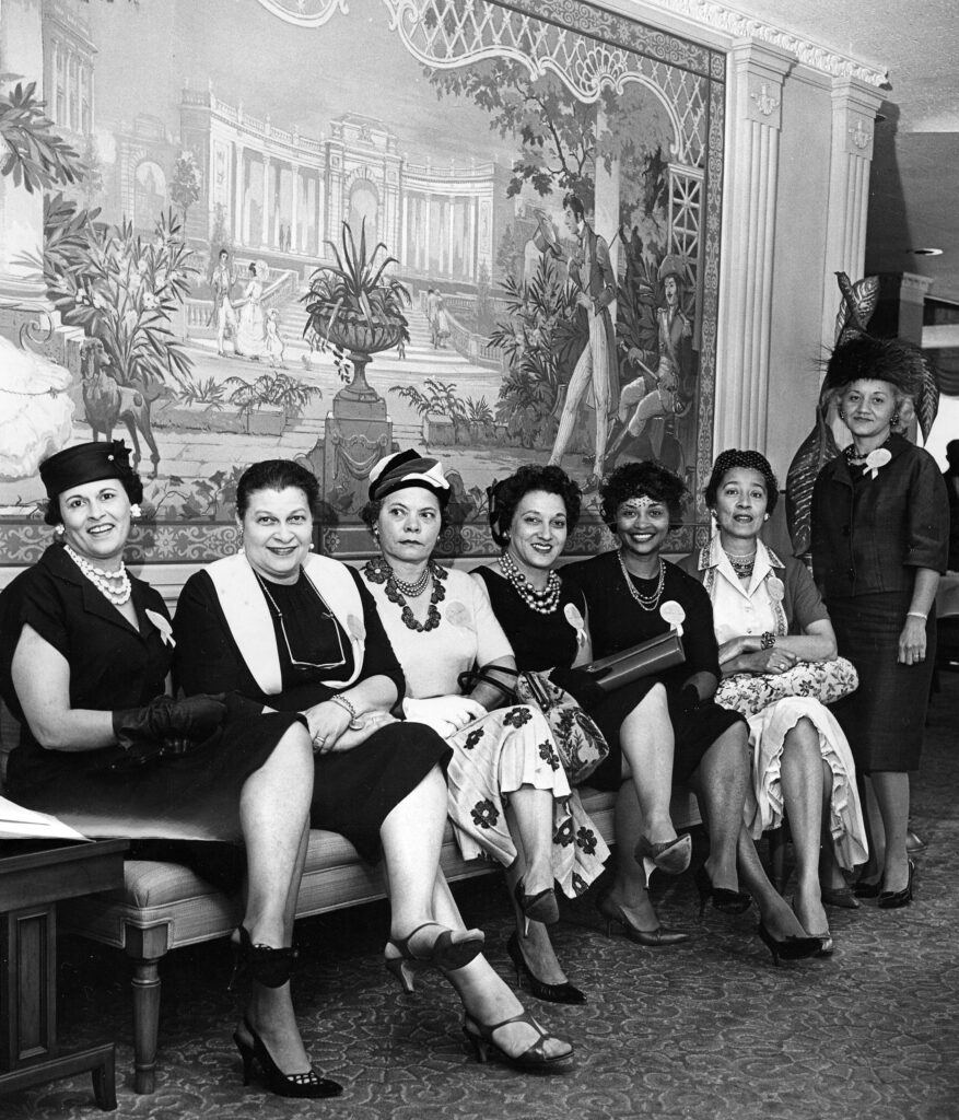 A black and white photos of Cleveland Society Ladies posing for a proper seated picture, legs crossed