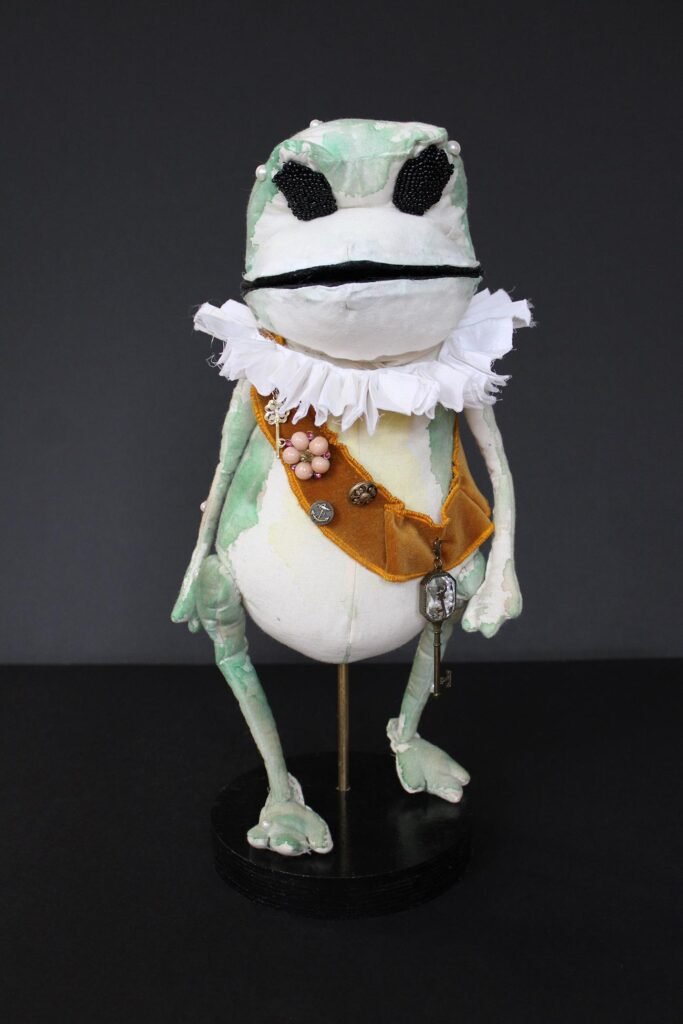 A frog puppet wearing a sash