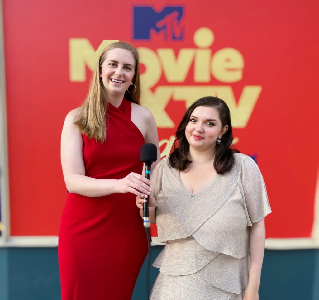 women hold mic in front of MTV Movie X TV Awards logo