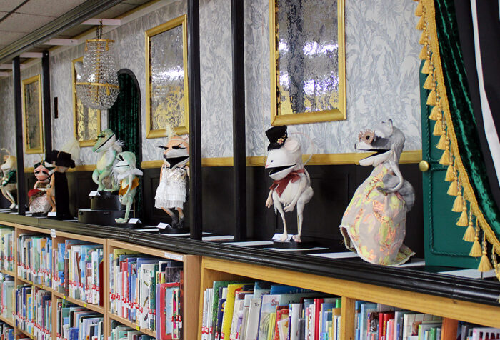 Puppets stand atop a library bookshelf