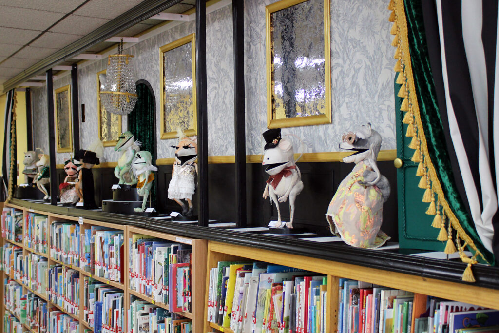 Puppets are spread out atop a library bookshelf