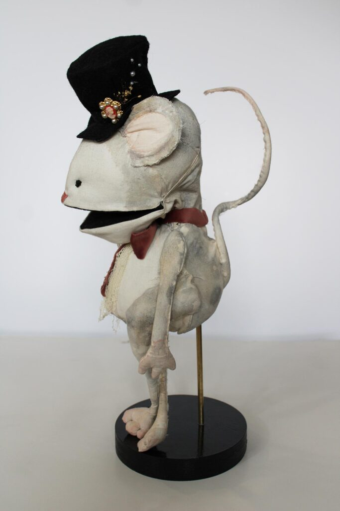 A mouse puppet sideways shows its tail