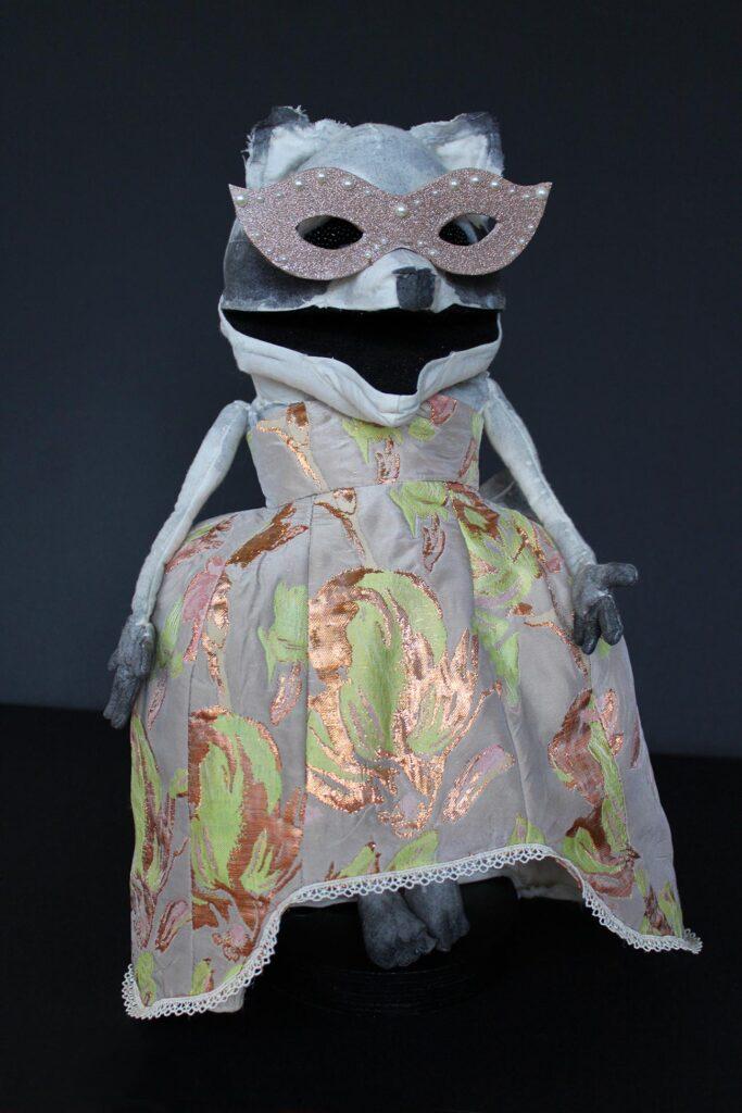 A raccoon puppet wearing a gown