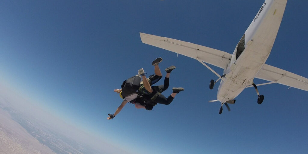 woman jumps from airplane while holding on to other diver