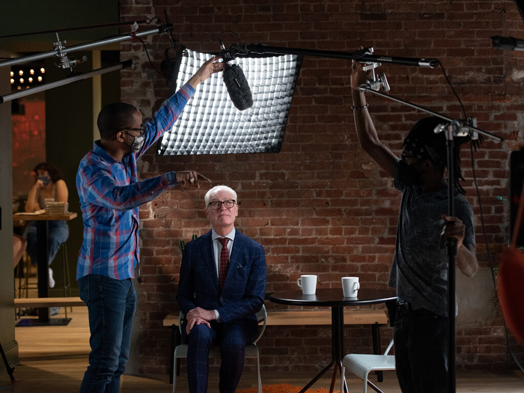 Two crew members test light and sound as Tim Gunn looks up