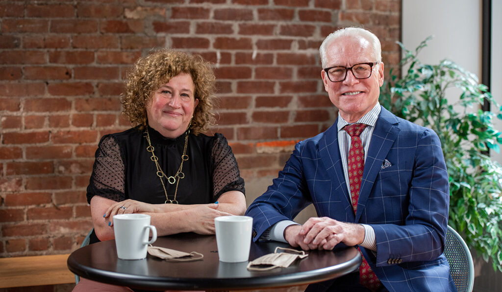 Sharon Topper and Tim Gunn seated at table in front of brick wall