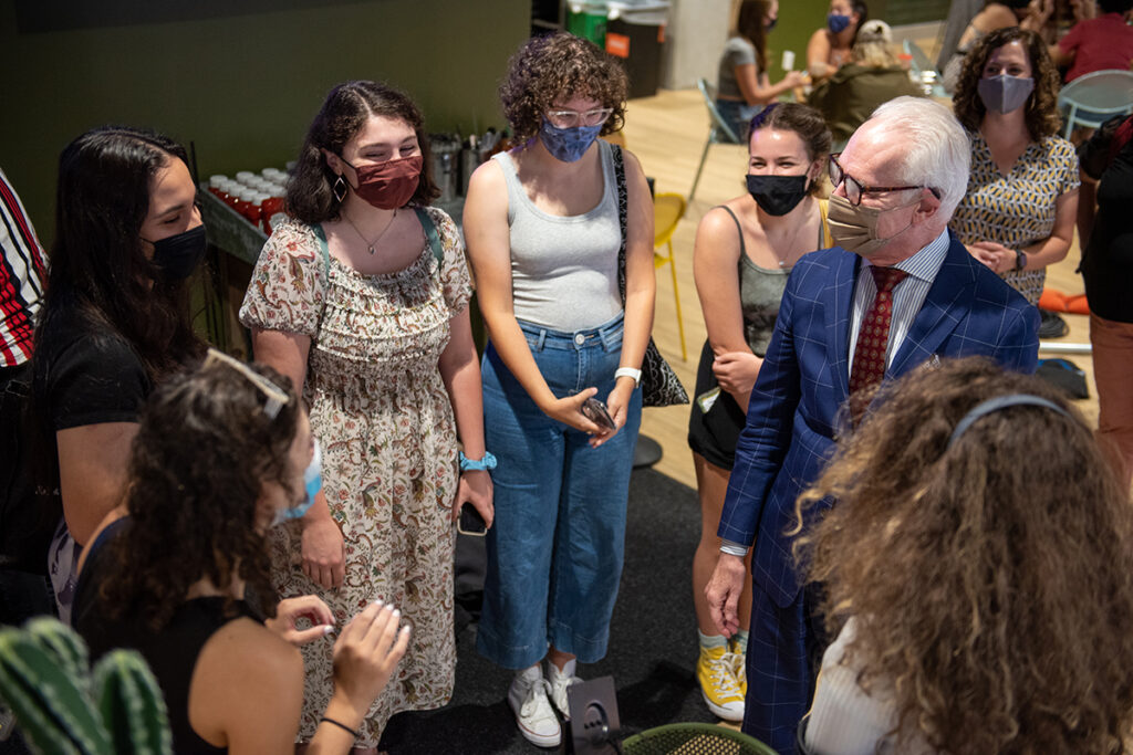 Tim Gunn surrounded by students, all wearing face masks.