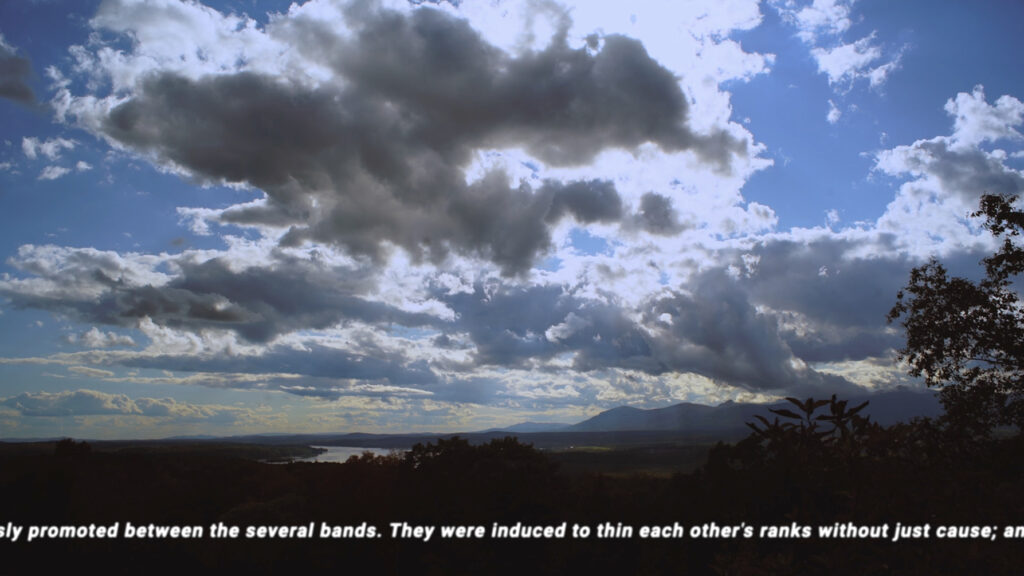 clouds rolling in over landscape, with text superimposed at bottom of image