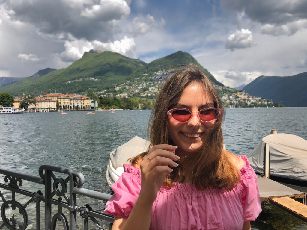 A woman smiles with a lake and green mountain in the background
