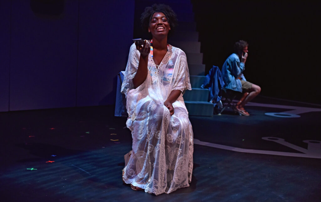 One woman wears a nightgown on stage