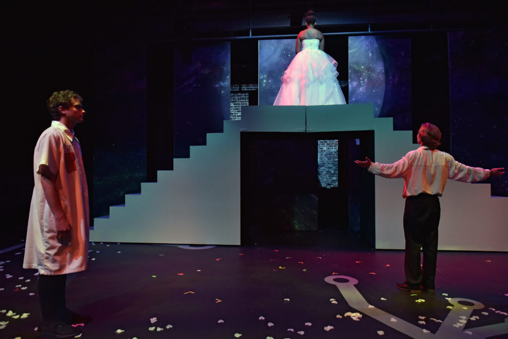 One woman wearing a wedding dress is atop the flight of a stairs while two men are one level below her, looking up at her