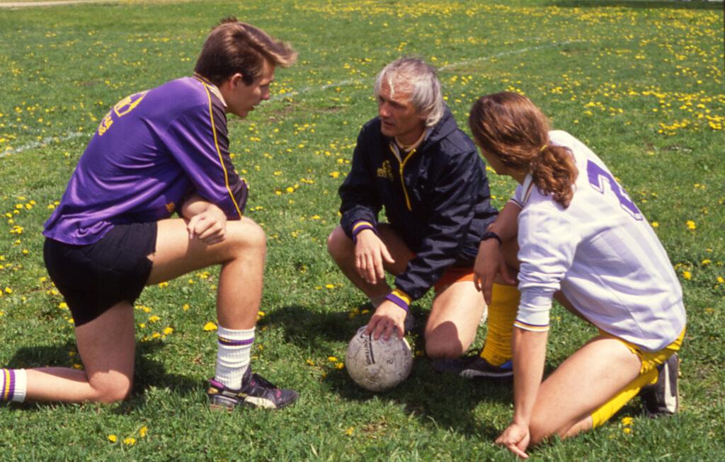 three men kneel on a soccer field