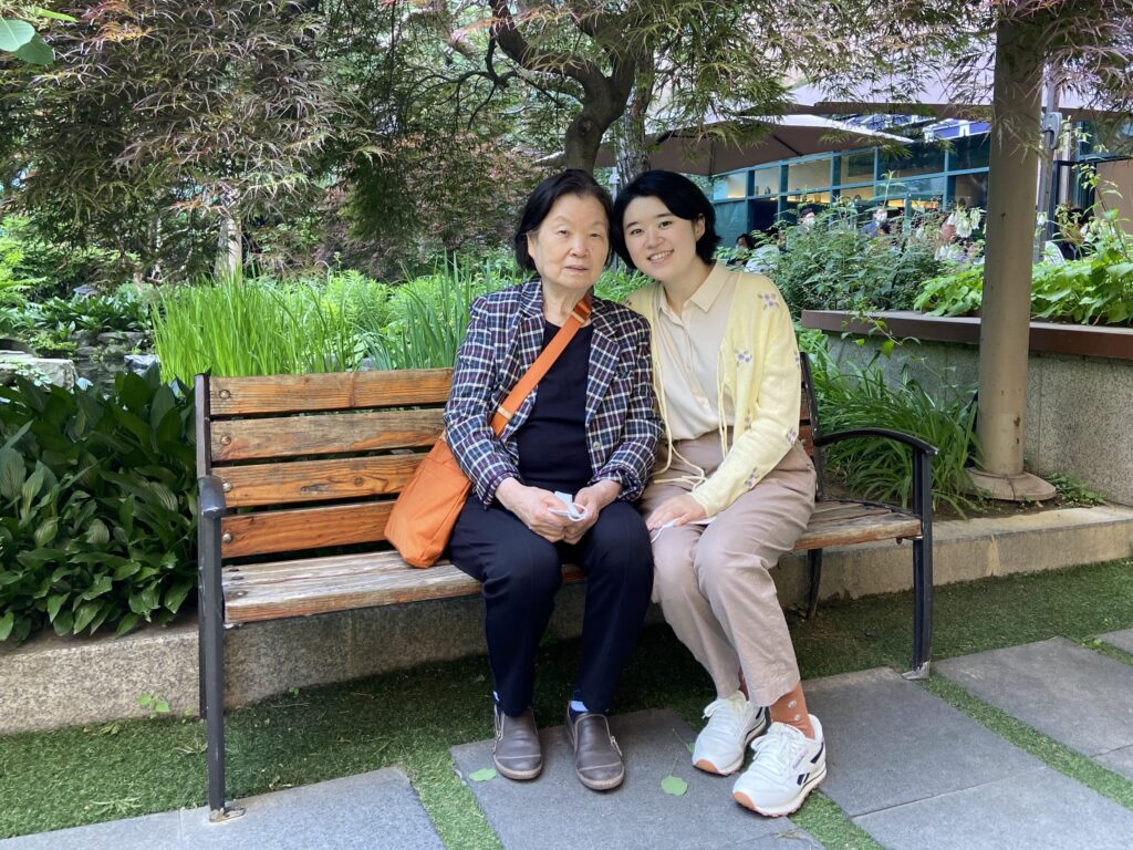 A woman sits with her grandmother on a bench
