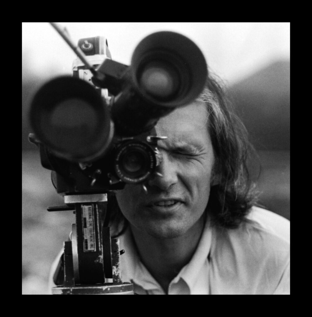 man looks through film lens