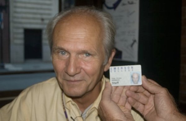 headshot of man with his photo ID in foreground