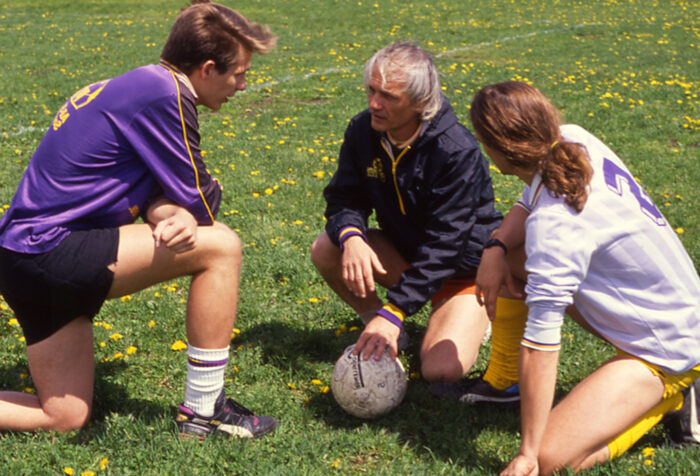 Three men kneel together on the soccer field. Two players and one coach.
